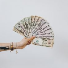 hand holding fan of us dollar bills